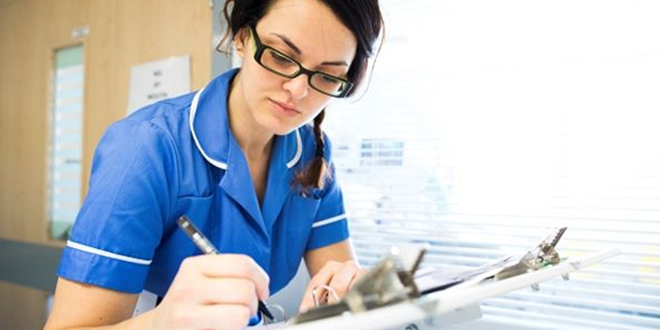 Nurse completing a forms for a patient